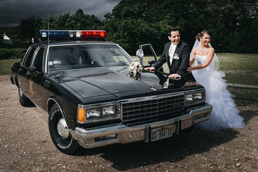 couple de jeunes mariés devant une voiture de police américaine
