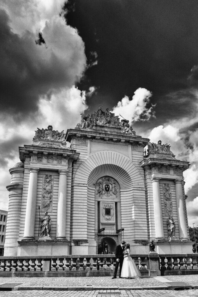 Couple de jeunes mariés devant la porte de Paris à Lille